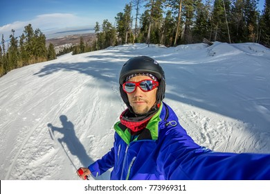 Man skier taking selfie photo with smart cell phone camera.