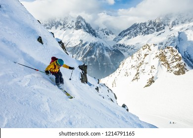 A man is skiing down the hill on the steep slope in Alps. Chamonix. High mountain area.