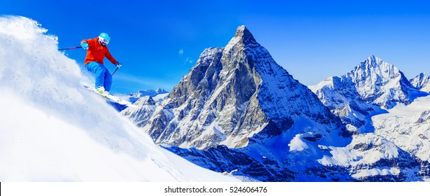 Man skiing on fresh powder snow with Matterhorn in background, Zermatt in Swiss Alps.