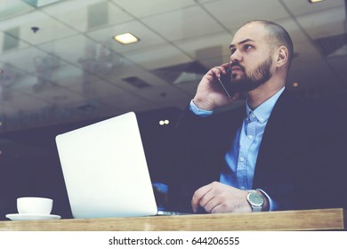 Man skilled lawyer is talking with his client via mobile phone before important court session,while is sitting with laptop computer in modern interior. Serious male financier is calling with cellphone