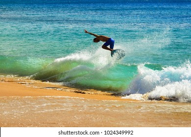 Man skim boarding on a wave