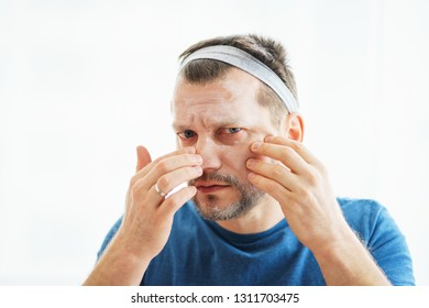 Man skin care. Attractive man put on a skin mask. Cosmetic procedures for men. Age and skin aging. Care about appearance and health. Man examines his skin.