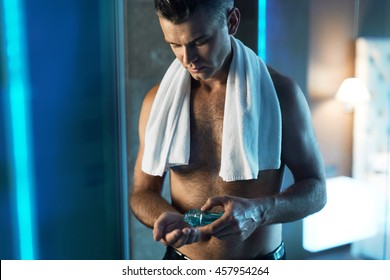 Man Skin Care Concept. Portrait Of Handsome Man With Naked Upper Body Pouring, Applying Lotion Into His Hand Standing In Bathroom.