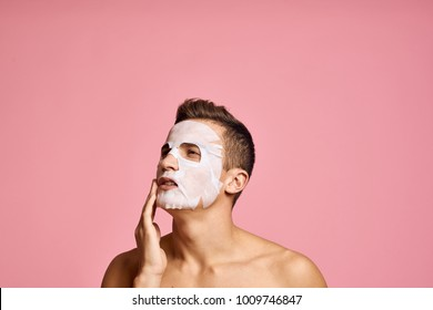 man in a skin care mask on a pink background