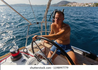 Man skipper runs a sailing yacht on the Sea.