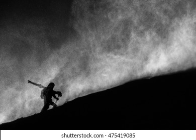 man with skis hiking up a mountain in a blizzard