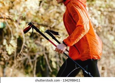 man skyrunner with trekking poles in hands in orange windbreaker