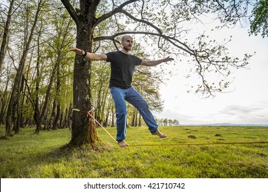 Man slacklining walking and balancing on a rope