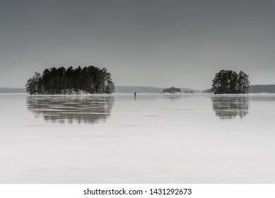 Man sledging on frozen lake in between two islands