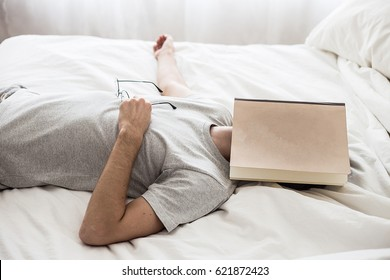 Man sleep with book covering him face