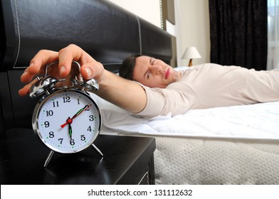 A man is sleeping with an alarm clock in front