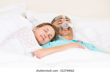 Man with sleeping apnea and CPAP machine, devise, asleep peacefully with wife in bedroom their house. Healthcare management patient with sleep apnea. Human respiratory, airway, system health issues.