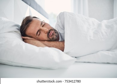 Man sleeping in bed with soft daylight. Sleep or rest concept.