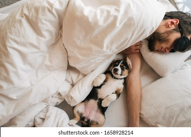 man sleeping with dog in white bed