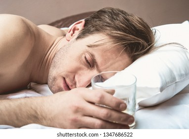 man sleeping with glass of alcohol in hand. Alcohol addiction.