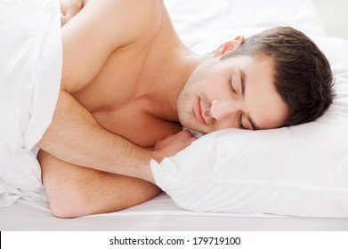 Man sleeping. Handsome young shirtless man sleeping while lying in bed