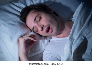 Man is sleeping in his bed at night