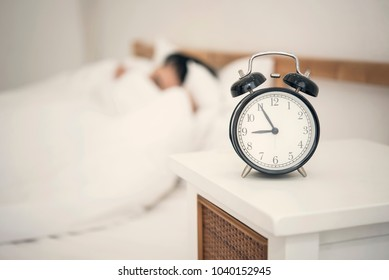 Man sleeping on bed in bedroom and alarm clock. wake up concept.