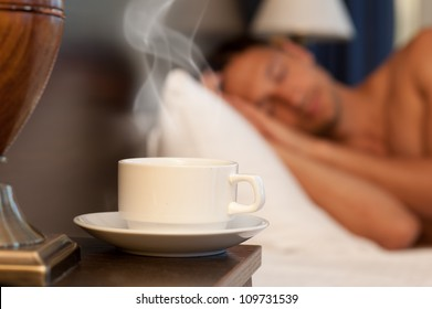 man sleeping on a bed, a cup of hot steaming coffee on the bedside table and lamp