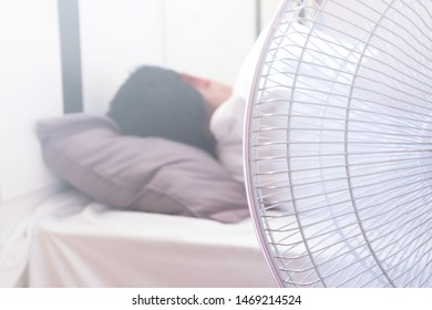 A man Sleeping on the bed and turn on the fan over the head risks of respiratory system.Health and medical care concepts