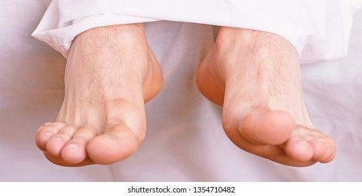 Man sleeping on bed under blanket. Sleep alone. Healthy skin on foot. Size of foot. Male feet on bed in morning. Fresh and relaxed. Health and wellbeing concept. Feet appear out of blanket close up.