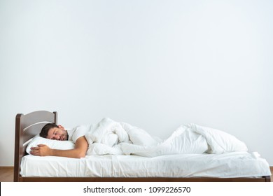 The man sleeping on the bed on the white background