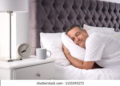 Man sleeping on comfortable pillow in bed at home