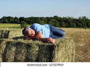 Man sleeping on a hay bale with the field and sky in the background