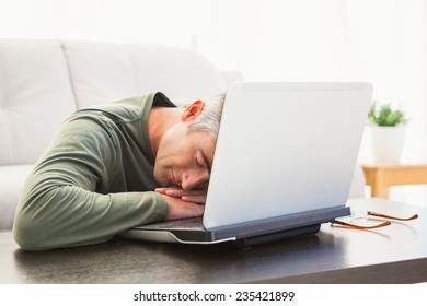 Man sleeping on his laptop at home in the living room