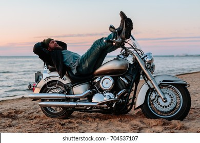 Man sleeping on a motorcycle on the beach at sunset