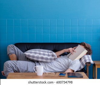 Man sleeping on old sofa with book covering his face because reading boook with preparing exam, education concept