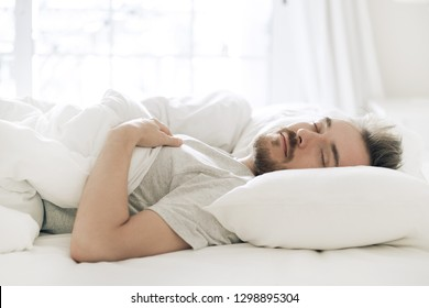 Man sleeping on the pillow on his back in white bed in the morning. Relaxed young bearded adult in cozy white bedroom taking a nap