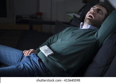 Man sleeping and snoring in front of television on the couch