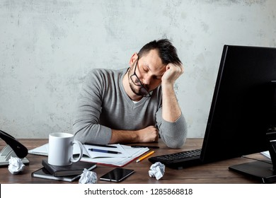 A man, a man sleeping at a table in the office. The concept of office work, a lot of work, fatigue, laziness. Copy space.