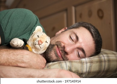 A man sleeping while cuddling a toy tiger.