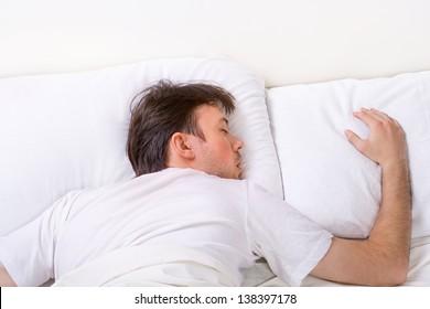 Man sleeps on bed with very deep sleep