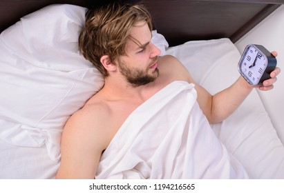Man sleepy drowsy unshaven bearded face covered with blanket having rest. Stick sleep schedule same bedtime and wake up time. Sleep regime habits concept. Man unshaven lay awake bed hold alarm clock.