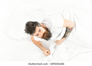 Man with sleepy face get up on bed, white sheets