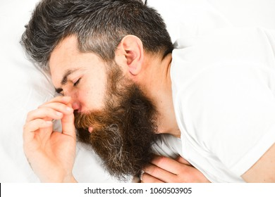 Man with sleepy face lies on pillow. Deep sleep concept. Man with beard and mustache in deep sleep, white background. Hipster with beard fall asleep, sleeping, nap, dreaming, close up.