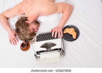 Man sleepy lay bedclothes while work. Writer used old fashioned typewriter. Author tousled hair fall asleep while write chapter top view. Workaholic fall asleep. Man with typewriter coffee lay bed.
