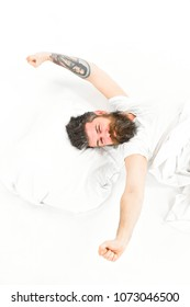 Man slept well, white background. Good morning concept. Hipster with beard stretching arms, energetic and successful macho, top view. Man with sleepy face stretching, wake up.