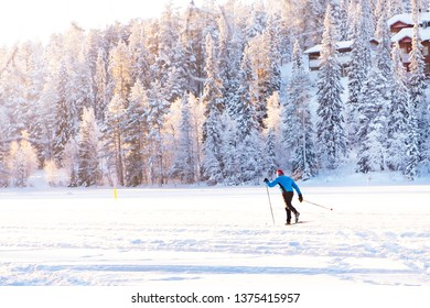 A man slides on skis on a snow-covered lake. Finland, sport and healthy lifestyle.