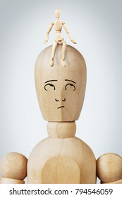 Man with a small another man sitting on his head. Abstract image with a wooden puppet