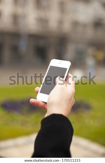 Man with smart phone in hand, urban street, blurred background