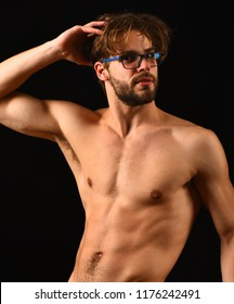 Man smart and sexy with beard and tousled hair wears eyeglasses. Man sexy muscular torso posing black background. Macho attractive nude guy nice belly six pack. Fit and attractive.