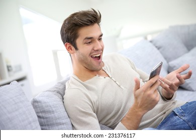 Man with smartphone being surprised as reading message