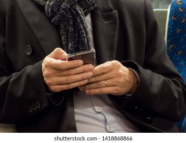 Man With Smartphone. Business man doing somethin with his mobile phone. Hands with smartphone and wedding ring. Man is going to the office in subway and doing something on his phone.