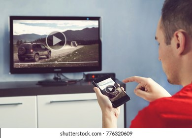 Man With Smartphone Connected To A TV Watching Video At Home. transfer video from phone to TV screen. Modern gadgets. Information transfer between devices over wifi.