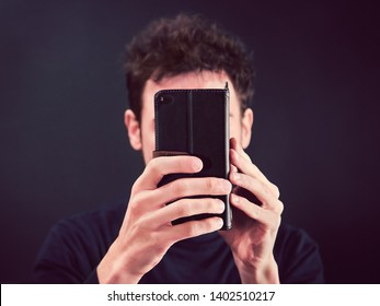 man with smartphone in front of face, front view of young person holding a mobile phone in hands (the Telephone covering his expression)