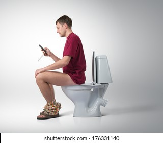 Man with smartphone sitting on the toilet